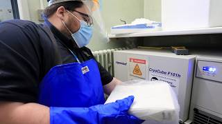 A pharmacy technician from Croydon Health Services takes delivery of the first batch of COVID-19 vaccinations at Croydon University Hospital in south London.