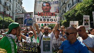 """متظاهر جزائري يرفع لافتة """"حرروا كريم طابو"""" أثناء مظاهرة شعبية أيلول/2019"""