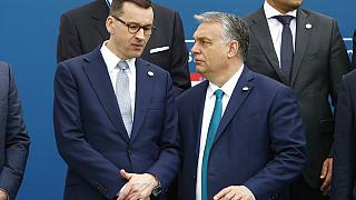 In this Feb. 1, 2020 file photo, Poland's PM Mateusz Morawiecki, left, and Hungary's PM Victor Orban speak as they line up for a group picture prior to a meeting in Beja
