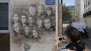 A woman wearing a face mask takes a pictures of a painting by French street artist Christian Guemy, a.k.a. 'C215' in Paris on Wednesday, Sept. 2, 2020.