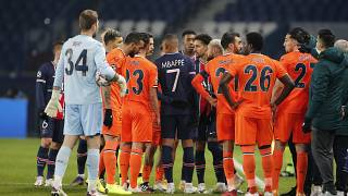 Players of Paris Saint Germain and Istanbul Basaksehir leave the pitch after an argument between the Turkish players and the fourth referee during a Champions League game.