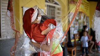 شاهد: السيدة سانتا كلاوس تلجأ لسترة معقمة لمعايدة الأطفال بمناسبة عيد الميلاد في البرازيل