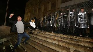 A protester throws a stone to police officers outside the Prime's Minister office during clashes in Tirana, Albania , on Wednesday, Dec. 9, 2020
