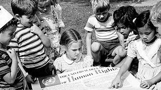 أطفال من الحضانة الدولية التابعة للأمم المتحدة ينظرون إلى ملصق للإعلان العالمي لحقوق الإنسان. (1950) ©الأمم المتحدة