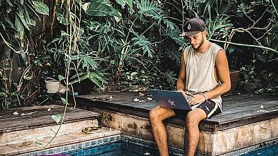 A young freelancer works by the pool at Dojo Bali Co-working camp