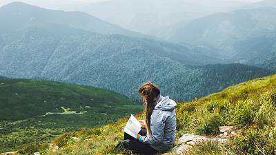 Reading climate fiction on the top of a mountain
