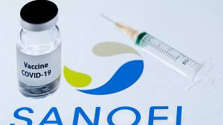 """زجاجة """"لقاح كوفيد-19"""" بجانب شعار شركة الأدوية البيولوجية الفرنسية سانوفي."""