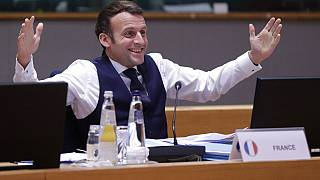 France's Macron gestures after an all night negotiating session at the EU summit saw agreement on cutting the bloc's greenhouse gas emissions by at least 55% by 2030