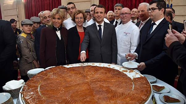 French president Emmanuel Macron (C) and his wife Brigitte (L) cut slices of a traditional epiphany cake during a ceremony at the Elysee palace, on January 12, 2018