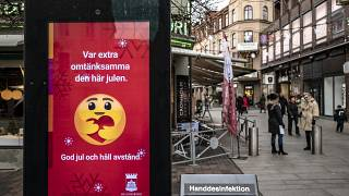 An public information sign wishing Merry Christmas and asking to maintain social distancing is seen in a pedestrian shopping street in Helsingborg, Sweden, Dec. 7, 2020.