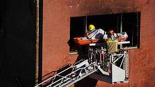 Firefighters load the body of a dead person into a crane after a fire on a building in Badalona, Barcelona, Spain,