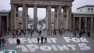 Students set up candles for the slogan'Fight for 1 point 5' during a protest of the Fridays For Future movement at the Brandenburg Gate Berlin, Germany