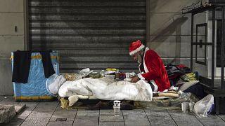 Un senzatetto, di nome Rafael, indossa un abito da Babbo Natale mentre si prepara a cenare sul ciglio di una strada, a Milano, giovedì 10 dicembre 2020