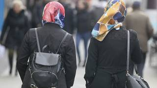 In this photo taken Friday, April 21, 2017 women with headscarfs are walking in a pedestrian zone in Vienna, Austria.