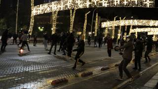 Protesters throw stones to riot police during clashes in Tirana