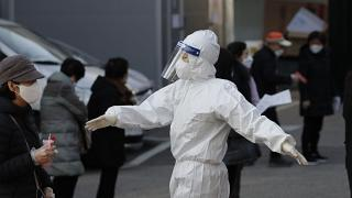 A medical worker wearing protective gear speaks as people wait in queue during testing for COVID-19 at a coronavirus testing centre in Seoul, South Korea.