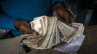Un trabajador muestra un fajo de pesos cubanos