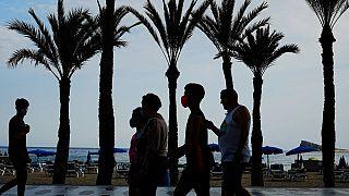 Un grupo de turistas, con mascarillas para prevenir la propagación del coronavirus, camina al lado de la playa en Benidorm, en el sudeste de España.