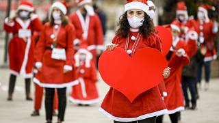 People dressed as Santa Claus take part in a charity event in Pristina.