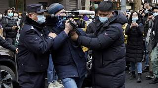 FILE PHOTO: A foreign journalist is blocked by Chinese policemen