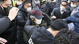 Cho Doo-soon, center, escorted by police officers, arrives home in Ansan, South Korea, Saturday, Dec. 12, 2020.