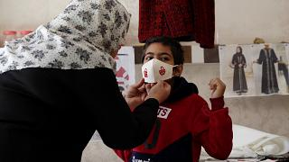 كمامات بألوان الميلاد مطرزة بأيدي مريضات سرطان في غزة