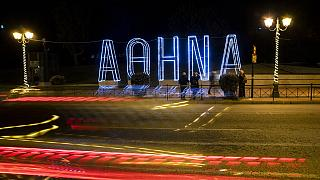Light tracks of passing cars are seen in front of a Christmas installation in Athens
