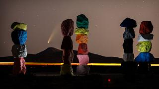 """The comet Neowise is visible in the evening sky above the artwork titled: """"Seven Magic Mountains"""" by artist Ugo Rondinone. Near Las Vegas, Nevada, USA. July 16, 2020"""