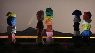 """La cometa Neowise dietro un'installazione artistica chiamata """"Le sette montagne magiche"""" di Ugo Rondinone, vicino Las Vegas, lo scorso 16 luglio"""