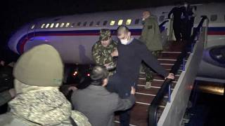 In this photo taken from the Russian Defense Ministry, an Armenian captive is escorted off a Russian military plane upon arrival outside Yerevan, Armenia, Dec. 14, 2020