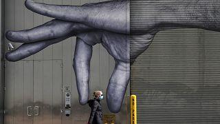 امرأة تمشي أمام لوحة جدارية ليد على جانب مبنى في وسط مدينة نيويورك، الولايات المتحدة.