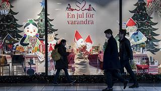 People walk past a Christmas themed shop window in central Stockholm, Sweden, Tuesday Nov. 10, 2020.