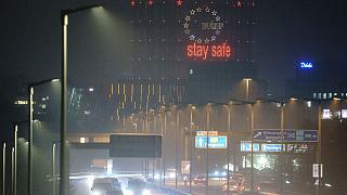 """Vehicles drive past the gasometer with the neon sign """"Stay Safe"""" on the city highway in the morning rush hour, in Berlin, Germany, Wednesday, Dec. 16, 2020."""