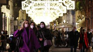 People wearing face masks to curb the spread of COVID-19 stroll along a shopping street decorated for Christmas, in downtown Rome, Monday, Dec. 14, 2020