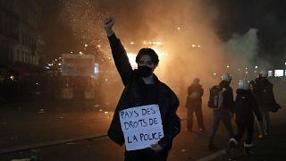 """متظاهر يحمل لافتة كتب عليها """"أرض حقوق الإنسان  الشرطة"""" خلال مظاهرة ضد قانون الأمن في فرنسا."""