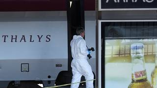 A member of the police forensics team takes part in an investigation next to a Thalys train on the platform at Arras train station, northern France, on Aug.22, 2015