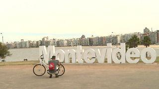 Un ciclista arregla su bicicleta con Montevideo al fondo, Montevideo, Uruguay