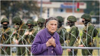 سيدة مسنة تمشي خلف جنود يقفون قبالة سياج شائكة أثناء مظاهرة في مينسك، بيلاروسيا. آب-أغسطس