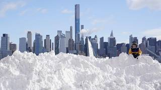 A boy plays on a mound of snow in front of the skyline of New York City