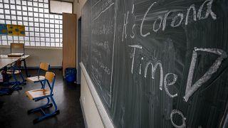 """""""It's Corona Time"""" is written on the chalkboard of an empty classroom of a high school in Frankfurt, Germany in March 2020."""