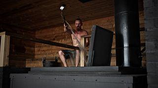الممثل الفنلندي جاسبر باكونن يلقي بالماء على الحجارة الساخنة داخل حمام الساونا الجديدة العصرية المسماة لويلي الفنلندية في هلسنكي.