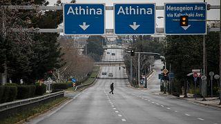 امرأة تعبر شارعًا يربط الضواحي الجنوبية لأثينا بوسط العاصمة ، في ضاحية أرجروبوليس. 22 مارس ، 2020