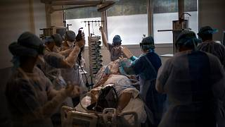 Medical workers begin installing a 60-year-old COVID-19 patient into an ICU room at the La Timone hospital in Marseille, France, Nov. 12, 2020.