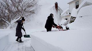 Residentes de Binghamton, estado de Nova Iorque, limpam entrada de casa após nevão