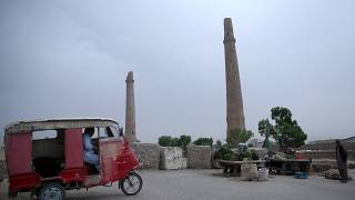 An Afghan rickshaw driver, left, waits for customers near the historical minarets in the center of Herat city, west of capital Kabul, Afghanistan, Tuesday, April 14, 2015.