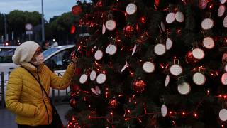 A woman takes a picture at messages adorning a Christmas tree outside Rome's Termini railway station, Thursday, Dec.10, 2020