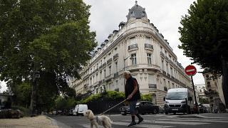 FILE - A man walks his dog next to an apartment building owned by Jeffrey Epstein in the 16th district in Paris, Tuesday, Aug. 13, 2019.