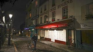 A man pushes his bicycle along a row of closed restaurants in Montmartre during the new imposed curfew in Paris, Tuesday, Dec. 15, 2020