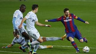 Barcelona's Lionel Messi, right, takes a shot at goal during the Spanish La Liga soccer match between Barcelona and Valencia at the Camp Nou stadium in Barcelona, Spain.