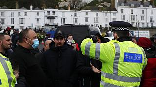 Truck drivers argue with police at entrance to the Port of Dover, that is blocked by police, as vehicles queue to be allowed to leave, in Dover, England